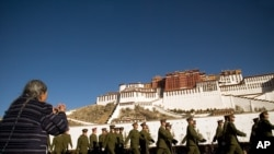 A woman prays as a group of Chinese soldiers march in front of the Potala Palace in Lhasa