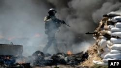Seorang tentara Ukraina mengambil posisi dalam pertempuran dengan milisi pro-Rusia di kota Slavyansk, Ukraina timur (24/4).