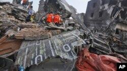 Para penyelidik memeriksa puing-puing pesawat Hercules milik Angkatan Udara yang jatuh di Medan (1/7). (AP/Binsar Bakkara)