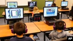 FILE - Students at a summer reading academy work in a computer lab at an Oklahoma City school, July 21, 2014.