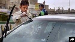 تحقیقاتی ادارے کا ایک اہلکار کراچی میں فائرنگ کا نشانہ بننے والے قوال امجد صابری کی گاڑی سے شواہد جمع کر رہا ہے (اے پی فوٹو)