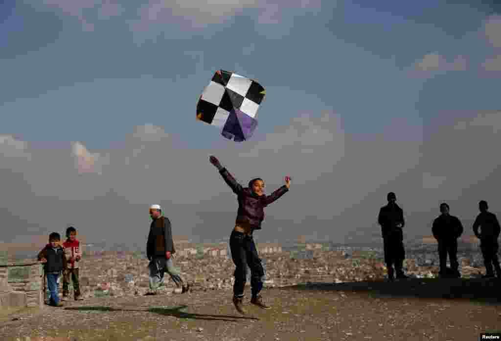 بادبادک بازی یک پسر بچه افغان بر روی تپه ای در کابل افغانستان