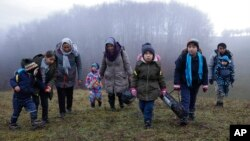 Two Afghan families walk in a clearing after leaving a Croatian forest near the Bosnian town of Velika Kladusa.