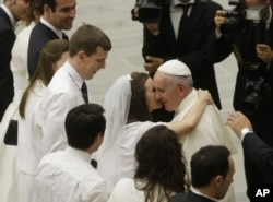 FILE - Pope Francis greets newlyweds during the general audience at the Vatican, Aug. 5, 2015. Pope Francis says divorced Catholics who remarry and their children deserve better treatment from the Catholic church.