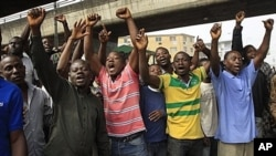 Angry youths protest and shout slogan in Lagos, Nigeria, Monday, Jan. 16, 2012. For the first time since protests erupted over spiraling fuel prices, soldiers barricaded key roads Monday in Nigeria's two biggest cities as the president offered a concessio