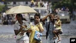 曼谷居民抱着孩子在被洪水淹没的街道上行走