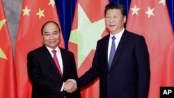 FILE - Chinese President Xi Jinping (right) poses with Vietnamese Prime Minister Nguyen Xuan Phuc prior to a meeting at Great Hall of the People in Beijing, Sept.13, 2016.