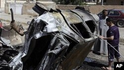 People inspect a destroyed car in front of the provincial council building of Tikrit, 80 miles (130 kilometers) north of Baghdad, Iraq, March 30, 2011