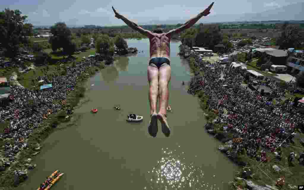 Spectators watch as a diver Sali Riza Grancina, winner of the competition, performs the winning jump from the Ura e Shenjte bridge during the traditional annual high diving competition, near the town of Gjakova, 100 km south of the Kosovo capital Pristina. A total of 27 divers from Kosovo competed, diving from the 22-meter-high bridge into the Drini i Bardhe River.