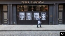 A man wearing a face mask to protect against the coronavirus walks past a closed Dolce & Gabbana store, Thursday, May 7, 2020, in New York. The U.S. economy lost 20.5 million jobs last month. (AP Photo/Mary Altaffer)