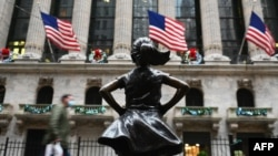 People walk past the New York Stock exchange (NYSE) and 'Fearless Girl' statue at Wall Street after heavy rainfall on November 30, 2020 in New York City. - Credit ratings giant S&P Global reached an all-stock deal to buy IHS Markit for $44 billion,…
