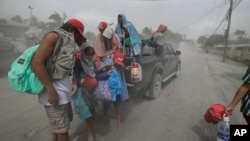 A family evacuates to safer grounds as Taal volcano in Tagaytay, Cavite province, southern Philippines on Monday, Jan. 13, 2020. (AP Photo/Aaron Favila)