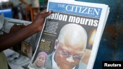 A man holds a newspapers following the death of Tanzania's President John Magufuli in Dar es Salaam, Tanzania, March 18, 2021.