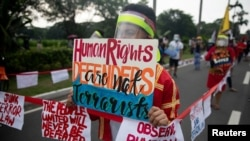 """A protestor, maintaining social distancing from others to prevent the spread of coronavirus disease (COVID-19), holds a placard that reads """"Human Rights Defenders are not terrorists"""" during a rally against the anti-terror bill in Manila."""