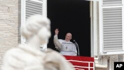 Pope Francis waves to the crowd from the window of his studio overlooking St.Peter's Square, at the Vatican, Sept. 1, 2019.