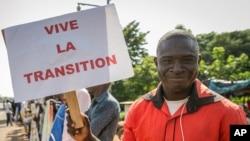 Un partisan tient une pancarte en français lisant «Vive la transition», à l'extérieur où une cérémonie de prestation de serment du président et du vice-président de transition a eu lieu, dans la capitale Bamako, Mali, vendredi 25 septembre 2020.