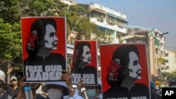 Anti-coup protesters display pictures of deposed Myanmar leader Aung San Suu Kyi in Yangon, Myanmar, Tuesday, March 2, 2021. Police in Myanmar repeatedly used tear gas and rubber bullets Tuesday against crowds protesting last month's coup, but the…