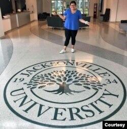 Renata Bilello is seen standing behind a Jacksonville University logo. (Courtesy - Renata Bilello)
