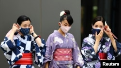 Women in traditional costumes, wearing protective face masks, walk outside the National Stadium, the main venue of the Tokyo 2020 Olympic Games, in Tokyo, Japan, Aug. 3, 2021.