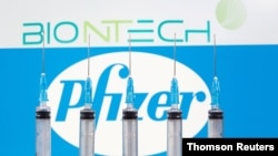 FILE - Syringes are seen in front of displayed Biontech and Pfizer logos in this illustration taken November 10, 2020.