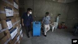 Dos trabajadores mueven un nuevo respirador artificial totalmente fabricado por empresas mexicanas.