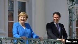German Chancellor Angela Merkel welcomes Italian Prime Minister Giuseppe Conte before a meeting at the German governmental guest house in Meseberg, outside Berlin, Germany, July 13, 2020.