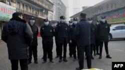 Petugas keamanan berdiri di depan pasar grosir makanan laut Huanan di kota Wuhan, provinsi Hubei, China yang ditutup, setelah otoritas kesehatan mengatakan seorang pria meninggal karena penyakit pernapasan setelah membeli barang-barang dari tempat tersebut (12/1/2020). (Foto:dok)
