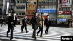 People cross a street in a business district in Tokyo, Japan.
