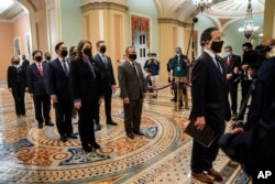 FILE - Democratic House impeachment managers stand before entering the Senate Chamber as they deliver to the Senate the article of impeachment alleging incitement of insurrection against former President Donald Trump, in Washington, Jan. 25, 2021.