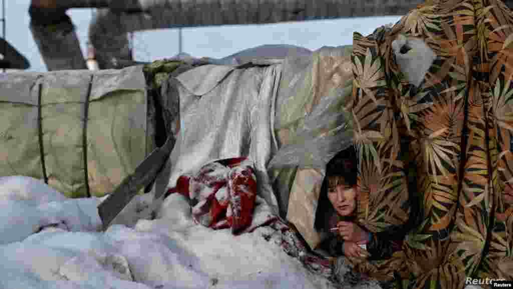러시아 옴스크에서 노숙자 여성이 임시 천막 사이로 얼굴을 내밀고 있다.