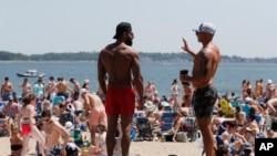 FILE - Two men talk as crowds gather on L Street Beach in the South Boston neighborhood of Boston.
