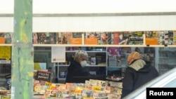 Seorang penjual koran mengenakan masker di tengah kebijakan pemerintah Italia membatasi mobilitas warga untuk mengatasi wabah virus corona di Milan, Italia, 14 Maret 2020. (Foto: Reuters)