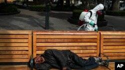 Një punonjës spërkat me dezinfektant, ndërsa një i pastrehë fle në një stol (Santiago, Kili, 15 prill 2020)