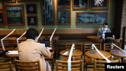 Tables and chairs are taped up to keep social distancing at a Starbucks coffee shop, following the novel coronavirus disease (COVID-19) outbreak, in Hong Kong, China April 2, 2020. REUTERS/Tyrone Siu