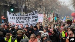 Demonstrators march with banners during a protest against pension reform plans in Paris, Dec. 28, 2019.