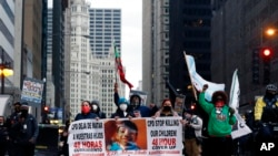 Protesters holding signs navigate along Chicago's South Michigan Avenue during a peaceful protest, April 14, 2021, ahead of the video release of the fatal police shooting of 13-year-old Adam Toledo.