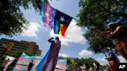 FILE - Demonstrators gather on the steps to the State Capitol to speak against transgender-related legislation bills being considered in the Texas Senate and Texas House in Austin, Texas, May 20, 2021.