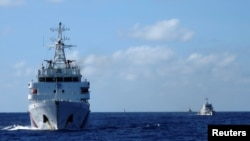 FILE - Chinese coastguard ships give chase to Vietnamese coastguard vessels (not pictured) after they came within 10 nautical miles of the Haiyang Shiyou 981, known in Vietnam as HD-981, oil rig in the South China Sea, July 15, 2014.