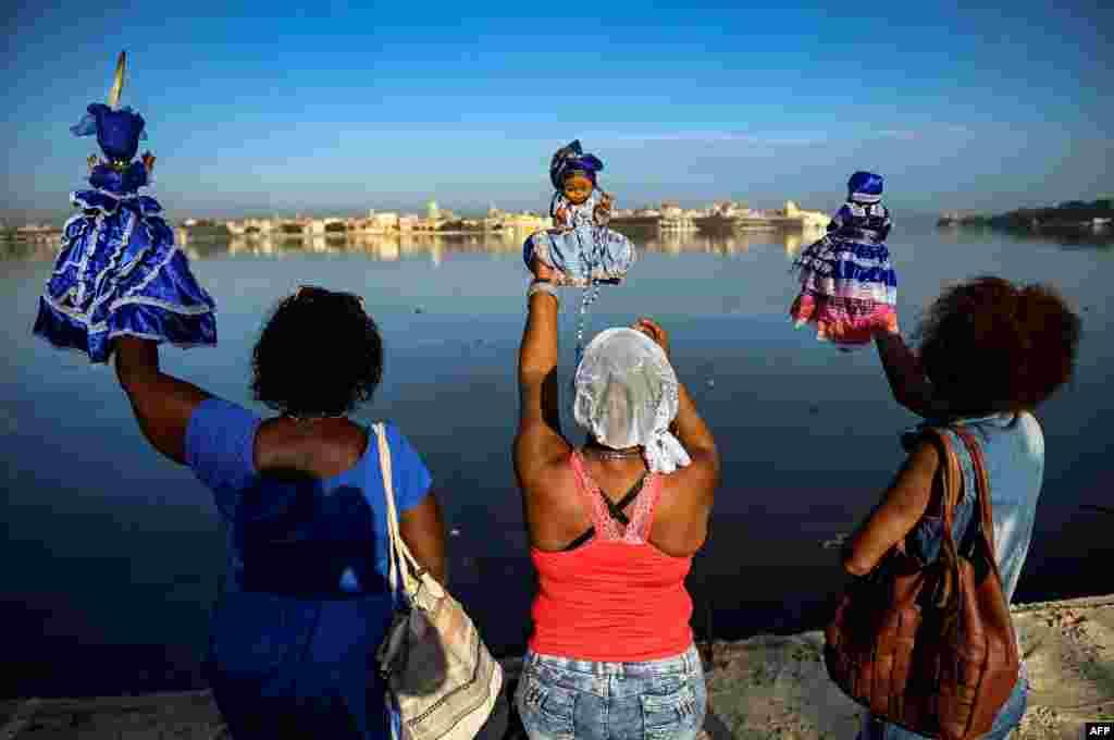 Followers of the Yoruba sea goddess Yemaya, give offering at the Havana harbor during Yemaya Day celebrations in Havana, Cuba.