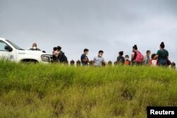 FILE - Asylum-seeking migrants from Central America are processed by the U.S. Border Patrol agents after crossing the Rio Grande into the United States from Mexico, in Penitas, Texas, July 8, 2021.