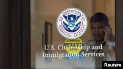 Un guardia de seguridad observa a través de la puerta cerrada de una oficina de inmigración en Nueva Jersey.