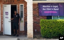 FILE - A security guard opens the door to the Whole Women's Health Clinic in Fort Worth, Texas, Sept. 1, 2021.