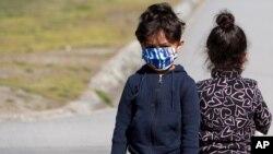 Deca migranata nose maske kako bi se zaštitila od zaraze Kovidom 19, tokom vakcinacije u centru za izbeglice u Krnjači, u Beogradu, 26. marta 2021. Srbija je započela sa vakcinacijom migranata. (Foto: AP)