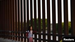 Una pequeña, que forma parte de un grupo de migrantes llegados de Centroamérica, camina junto a la valla fronteriza que separa EE. UU. y México, tras entrar al país de manera irregular, el 6 de abril de 2019.