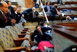 FILE - People shelter in the House gallery as protesters try to break into the House Chamber at the U.S. Capitol, Jan. 6, 2021, in Washington.