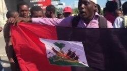 Manifestantes en el la vía del aeropuerto levantan la bandera roja y negra, un gesto desafiante, ya que es un símbolo de la dictadura-la bandera acutal de Haiti de roja y azul desde 1986-