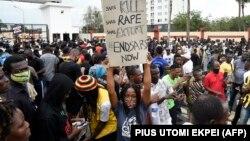 Une femme tient une pancarte lors d'une manifestation en cours pour appeler à la démolition de l'unité de police controversée à Ikeja, le 9 octobre 2020.
