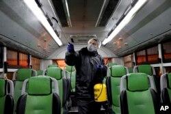 تہران میں حفاظتی کارکن ایک بس میں جراثیم کش ادویات کا چھڑکاؤ کر رہا ہے۔ 25 فروری 2020