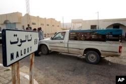 FILE - A van crosses the Tunisian-Libyan border of Dhuheiba, Tunisia, April 21, 2011.