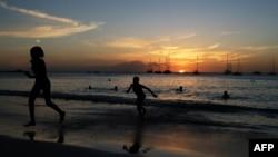ARCHIVO - Turistas en una playa de Bridgetown, Barbados, en el atardecer del 24 de marzo de 2017. Barbados ha anunciado su intención de convertirse en república en noviembre de 2021.